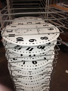 As the dials come out of bake, they are placed in racks to cool.  These are the 14 inch Arabic dials, ready to ship!